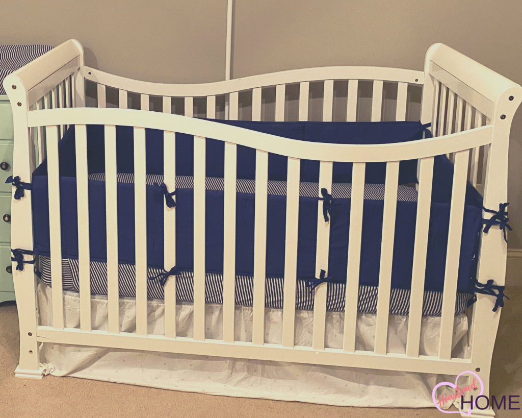 Close up of Crib, with navy and heather gray striped sheets.