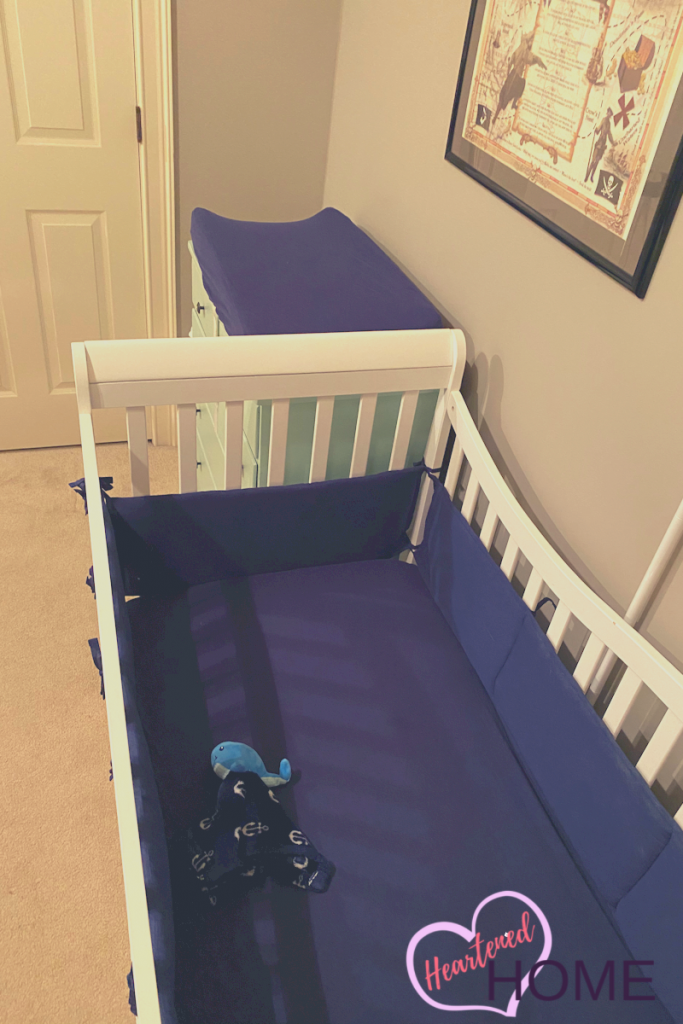 Crib view with navy sheets.