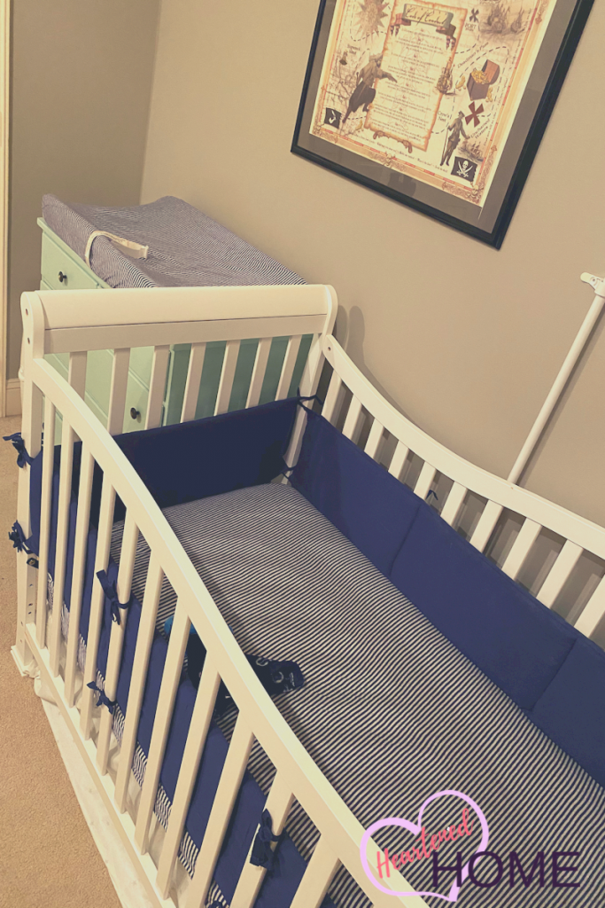 Crib view with alternate navy and heather gray striped sheets.