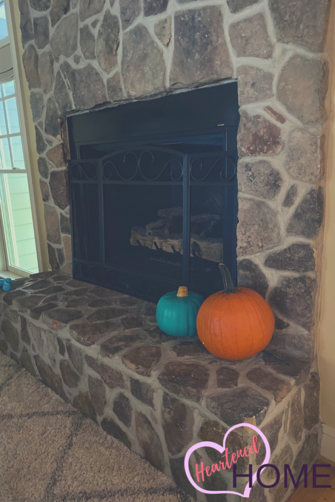 Real and faux pumpkins on the fireplace.